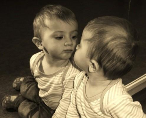 Foto eines Kleinkindes vor dem Spiegel als Symbol für Selbst-Erkenntnis